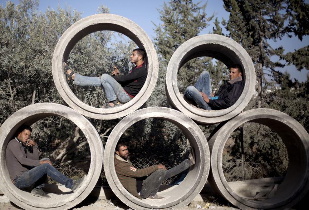 Muncitori palestinieni se odihnesc în conducte de beton, înaintea începerii programului de muncă, în Gaza, miercuri, 23 octombrie 2013.