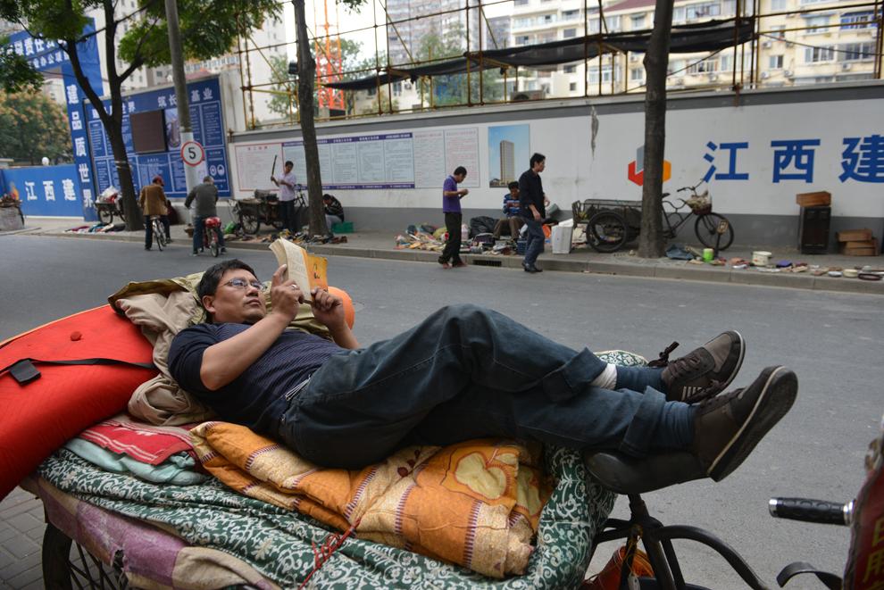 Un bărbat citeşte o carte, pe o stradă din Shanghai, China, miercuri, 30 octombrie 2013.