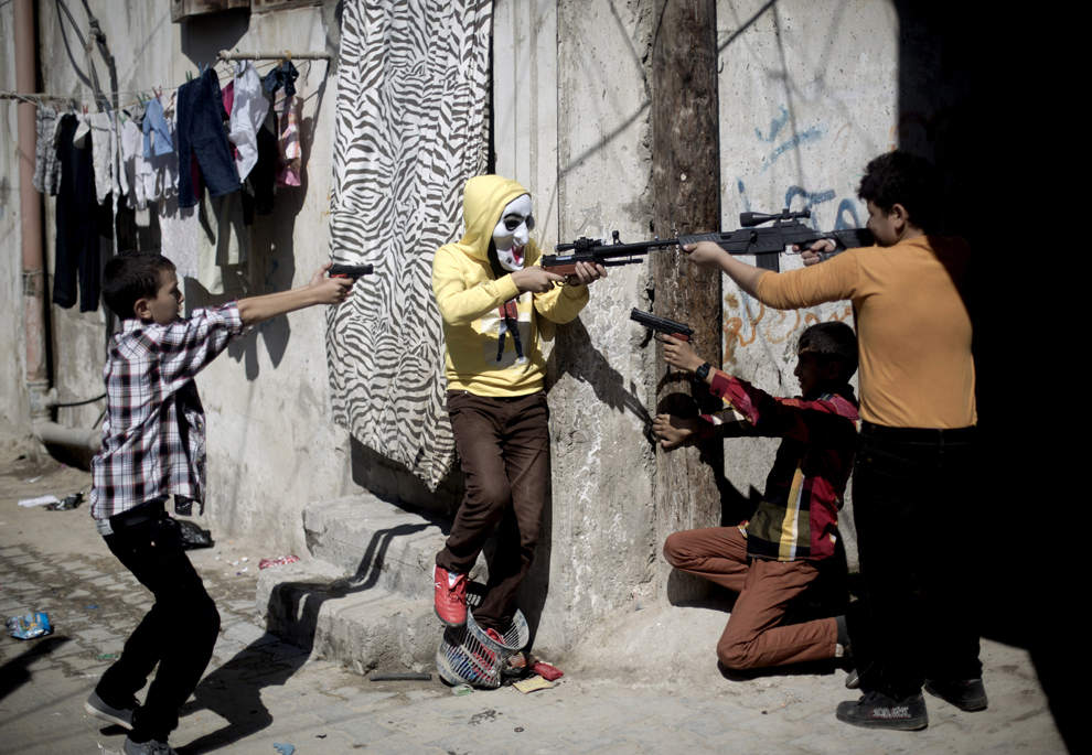 """Copii palestinieni se joacă cu arme de plastic, în timpul celei de-a doua zile a festivalului """" Eid al-Adha"""", în Gaza, miercuri, 16 octombrie 2013."""