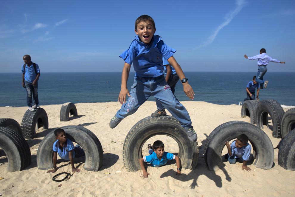 Copii palestinieni se joacă cu anvelope pe o plajă, în Deir al-Balah, Gaza, joi, 24 octombrie 2013.