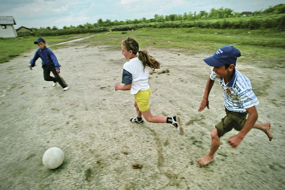 Letea, copii jucând fotbal în curtea şcolii.