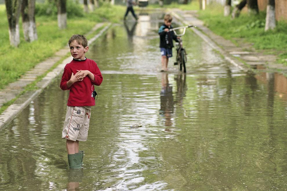 Maliuc, copii jucându-se pe aleea inundată după ploaie.