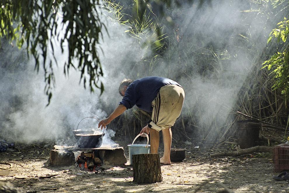 Se pregătesc raci fierţi în ceaun, razele conturează fuioare de fum.