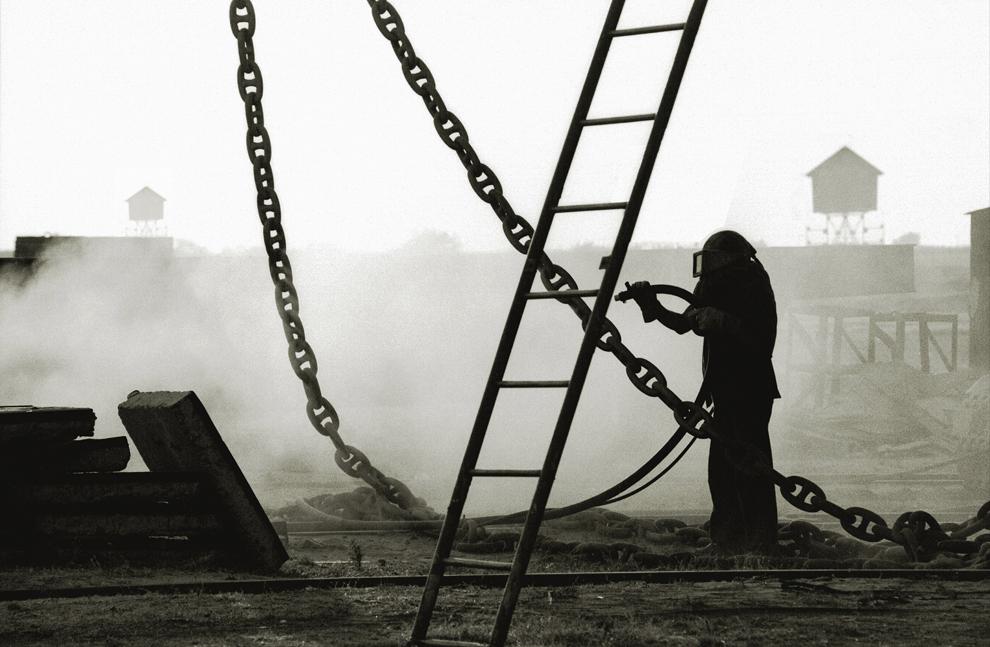 """Sulina, şantierul de reparaţii, """"scara îngerilor"""", un muncitor sablează un lanţ masiv."""