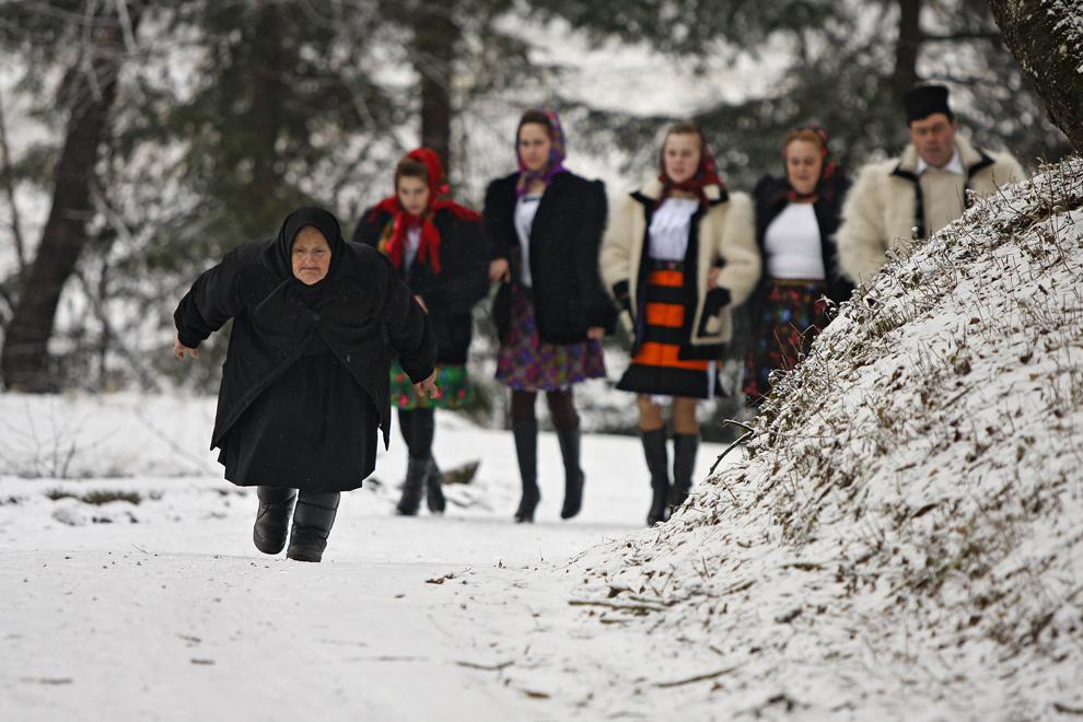 Persoane merg îmbrăcate în port tradiţional maramureşean la biserică pentru slujba de Crăciun, în satul Breb, judeţul Maramureş, duminică, 25 decembrie 2011.