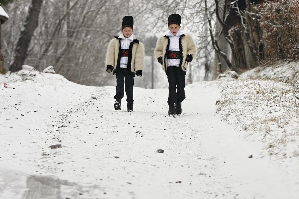 Doi copii merg îmbrăcaţi în port tradiţional maramureşean la biserică pentru slujba de Crăciun, în satul Breb, judeţul Maramureş, duminică, 25 decembrie 2011.