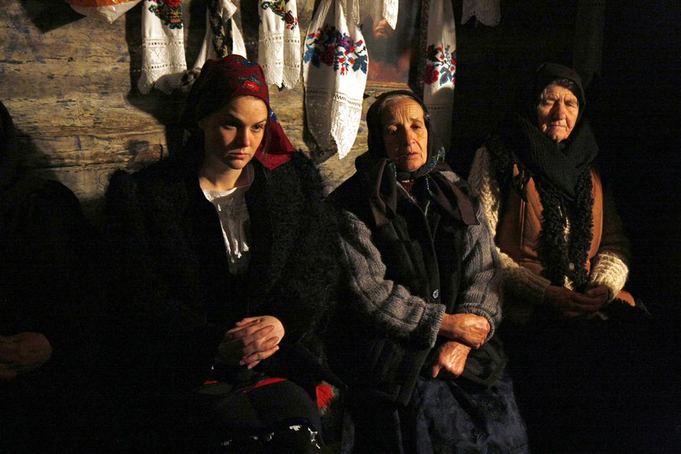 Persoane  îmbrăcate în port tradiţional maramureşean asistă la slujba de Crăciun, în satul Deseşti, judeţul Maramureş, duminică, 25 decembrie 2011.