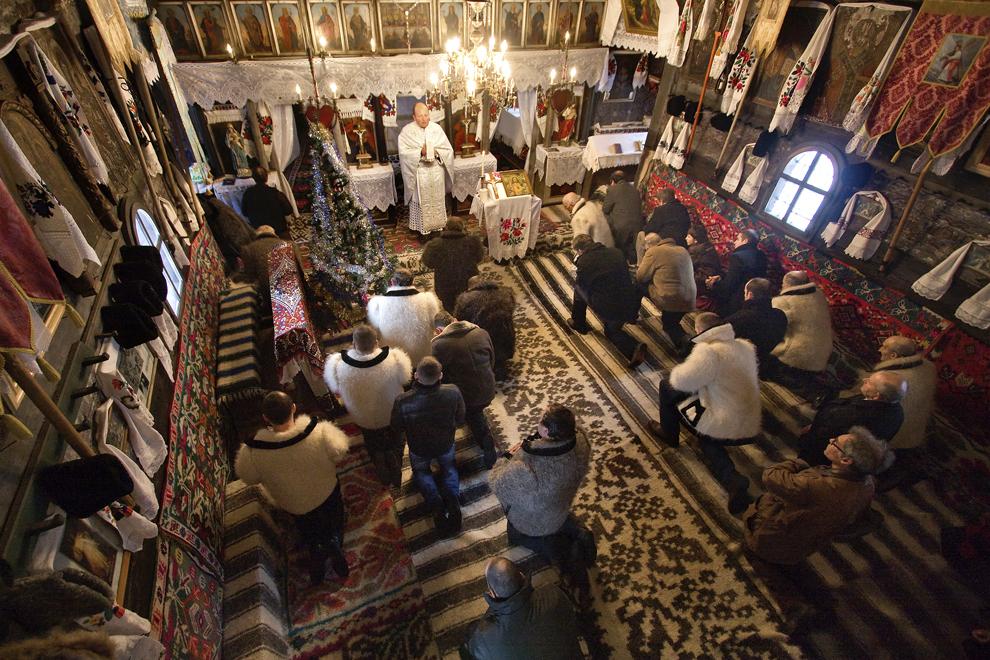 Persoane  îmbrăcate în port tradiţional maramureşean asistă la slujba de Crăciun, în biserica de lemn din satul Breb, judeţul Maramureş, duminică, 25 decembrie 2011.