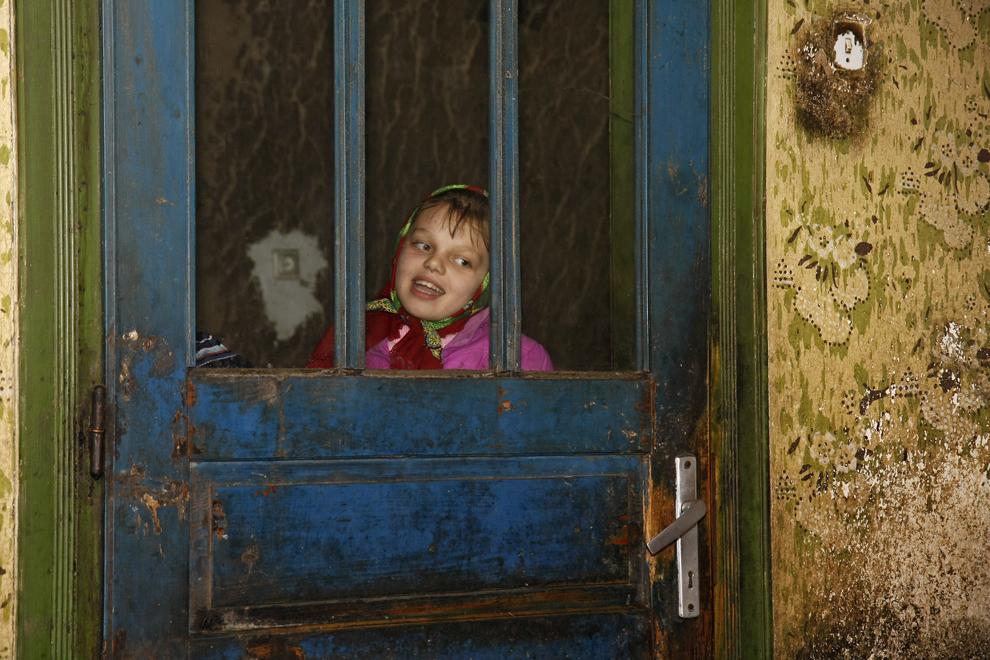 O fetiţă colindă la uşa unei case bătrâneşti din satul Breb, judeţul Maramureş, sâmbătă, 24 decembriei 2011.