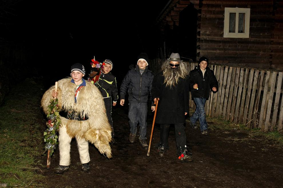 """Un grup de colindători merg cu """"Capra"""" pe uliţa satului Breb, judeţul Maramureş, sâmbătă, 24 decembriei 2011."""