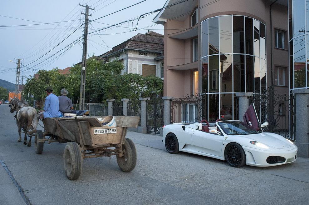 Certeze, Ţara Oaşului. O căruţă trece pe lângă Ferarri-ul lui Petre, un antrepenor de succes în Paris, venit în vacanţă în satul natal.