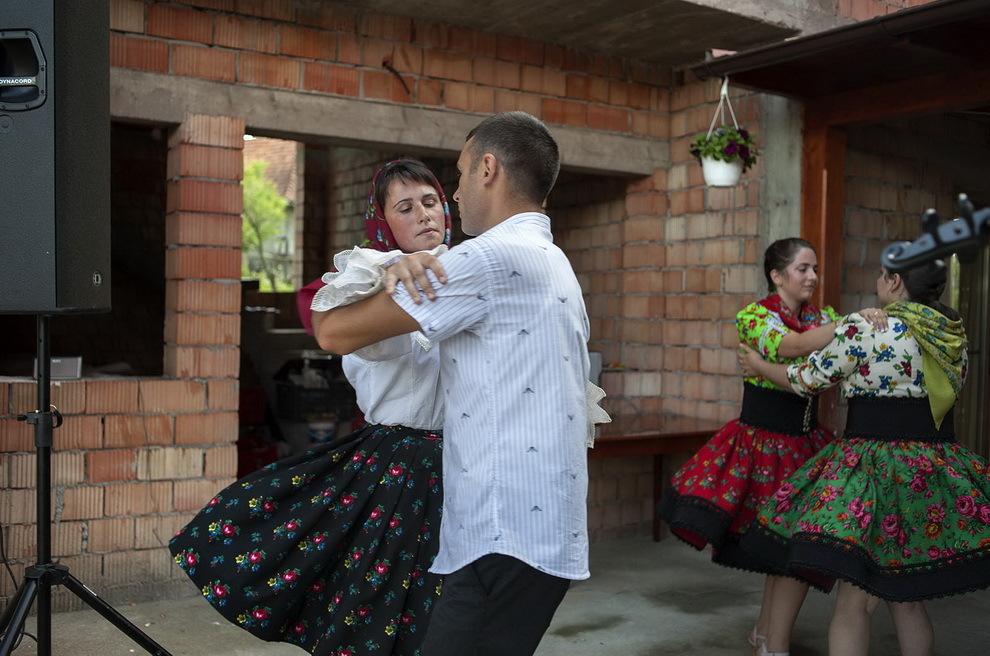 Târşolţ, Ţara Oaşului. Doi tineri dansează la o nuntă ce are loc lângă o casă în construcţie.
