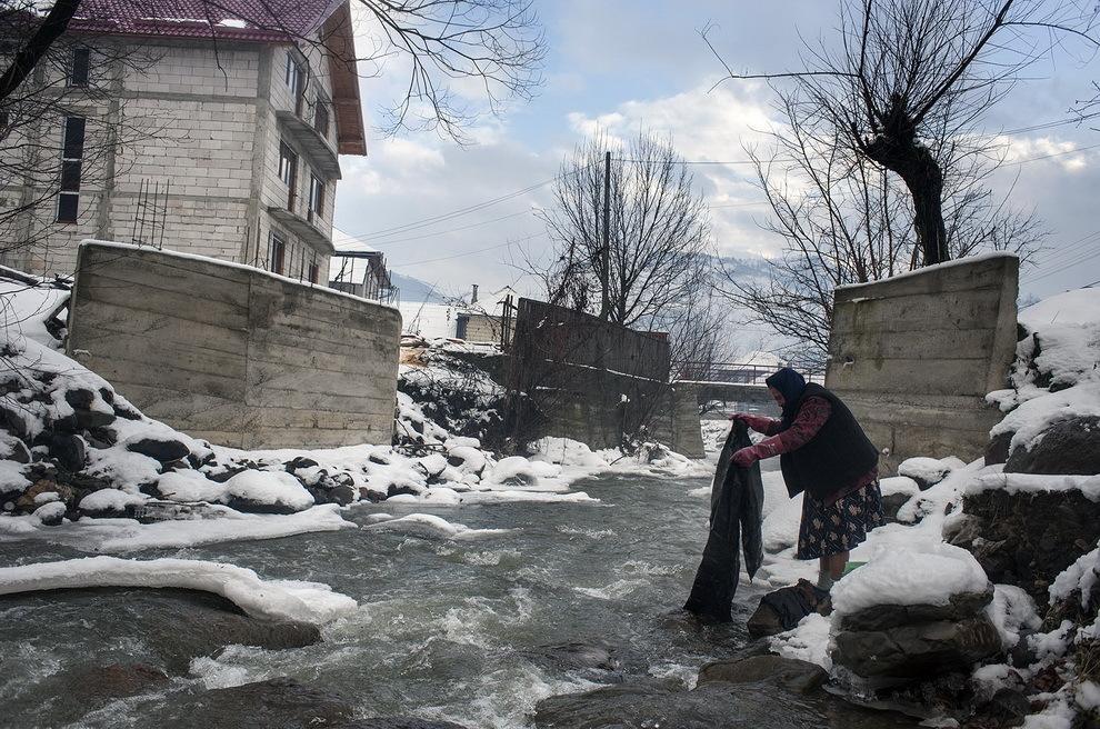 Botiza, Maramureş. O femeie clăteşte rufele la râu.