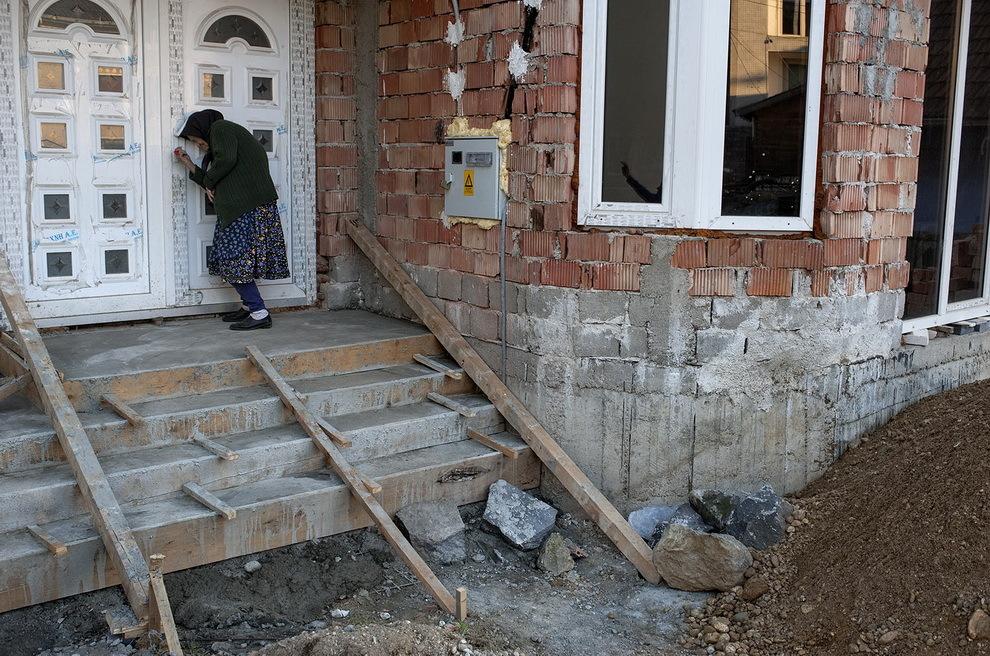 Moişeni, Ţara Oaşului. Gherman Maria se străduieşte să deschidă uşa casei recent construită de nepotul ei plecat la muncă în Franţa.