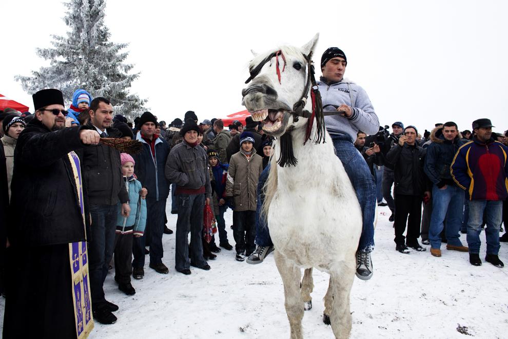 Un preot sfinţeşte caii înaintea cursei din satul Pietroşani, joi, 6 ianuarie 2011. Tradiţia din zonă este ca, în fiecare an, de Bobotează, preotul satului să boteze caii cu care sătenii se iau apoi la întrecere.