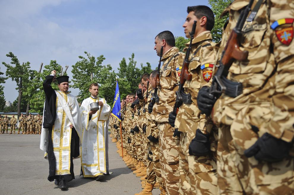 """Preoţi stropesc cu apă sfinţită cadrele militare prezente la ceremonia prilejuită de plecarea în teatrul de operaţiuni din Afganistan a Elementului de Comandă şi Control Zabul şi a Batalionului 2 Infanterie """"Călugăreni"""", în Bucureşti, joi, 19 mai 2011."""