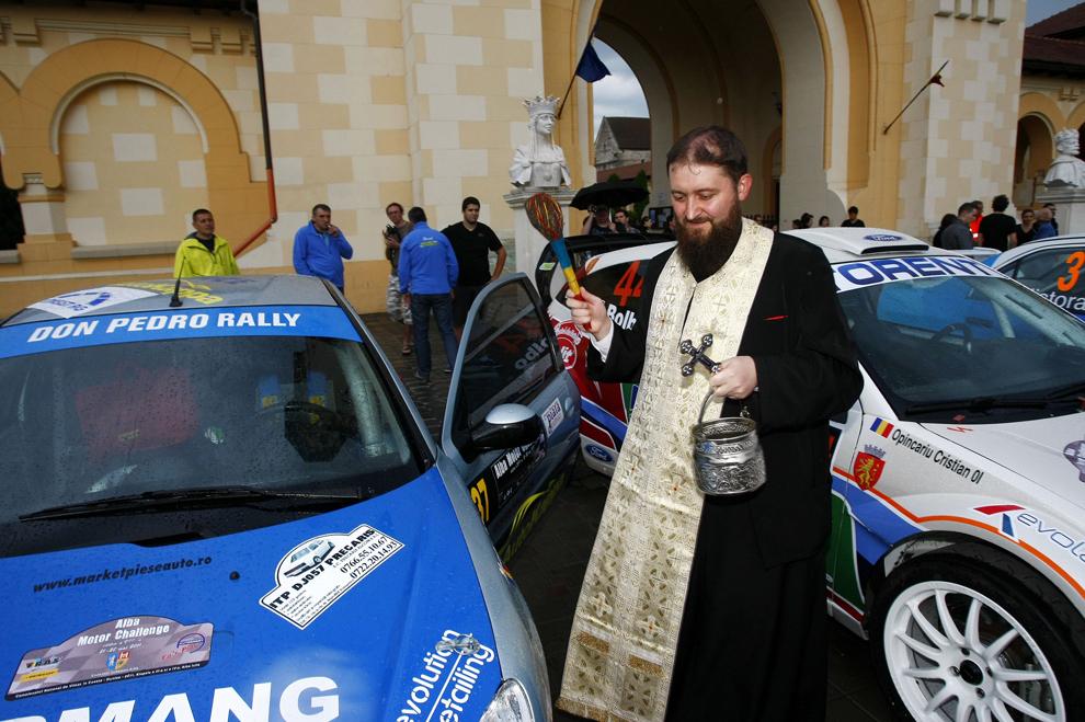 Un preot sfinţeşte maşinile de curse la Alba Motor Challenge 2011, etapa a IV-a, în cadrul Campionatului de Viteză în Coastă al României, lângă localitatea Straja, judeţul Alba, duminică, 22 mai 2011.