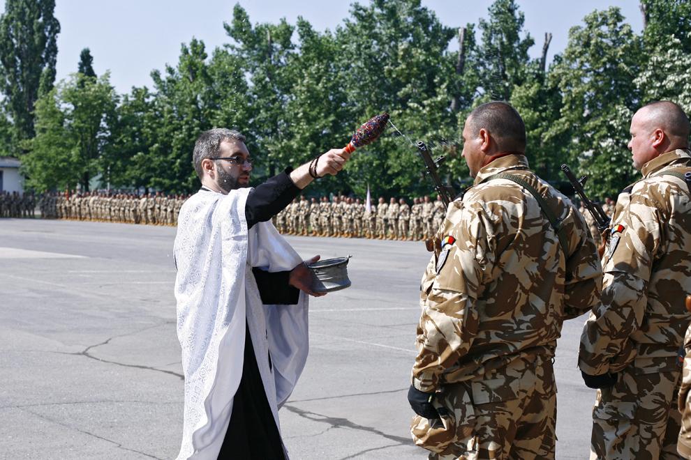 """Un preot stropeşte cu agheasmă militari în timpul ceremoniei prilejuite de plecarea în teatrul de operaţiuni Afganistan a Batalionului 495 Infanterie """"Cpt. Ştefan Soverth"""", în Bucureşti, joi, 16 iunie 2011."""