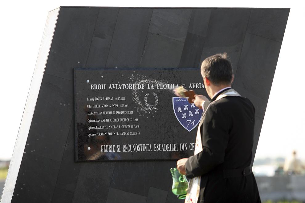 Un preot stropeşte cu apă sfinţită placa comemorativă a eroilor aviatori cazuţi la datorie, la ceremonialul de dezvelire a Monumentului Eroilor Aviatori de la intrarea în municipiul Câmpia Turzii, miercuri, 20 iulie 2011.