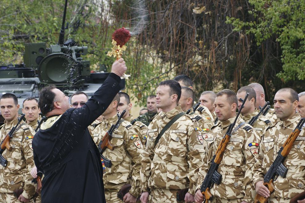 Un preot oficiază o slujbă, în timpul unei ceremonii militare prilejuite de plecarea în Afganistan a Companiei KAF GDA rotaţia a III-a, în Craiova, miercuri, 20 noiembrie 2013.