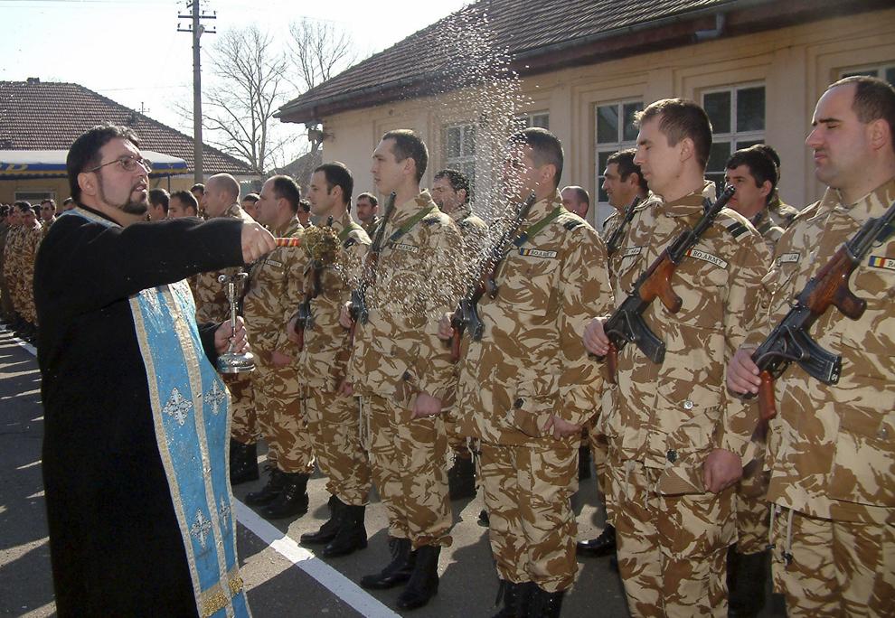 Un preot ortodox stropeşte cu apă sfinţită, luni 20 februarie 2006, capetele descoperite ale militarilor Batalionului 3 Constructii Mărăcineni prezenţi la ceremonialul dinaintea plecării în misiune în Irak.