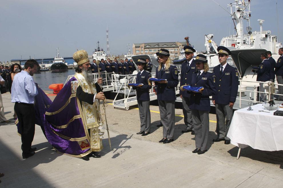 Un preot oficiază o slujbă religioasă, cu ocazia ceremonialului de intrare în serviciu a înca trei nave de patrulare aparţinând Poliţiei de Frontieră, în Constanţa, vineri, 30 iunie 2006.