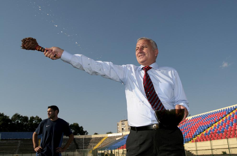 Finanţatorul echipei Gloria Buzău, Costel Bucur, stropeşte cu apă sfinţită terenul din Crâng pe care, duminică, se va disputa meciul cu Dinamo Bucureşti, la Buzău, joi, 26 iulie 2007.