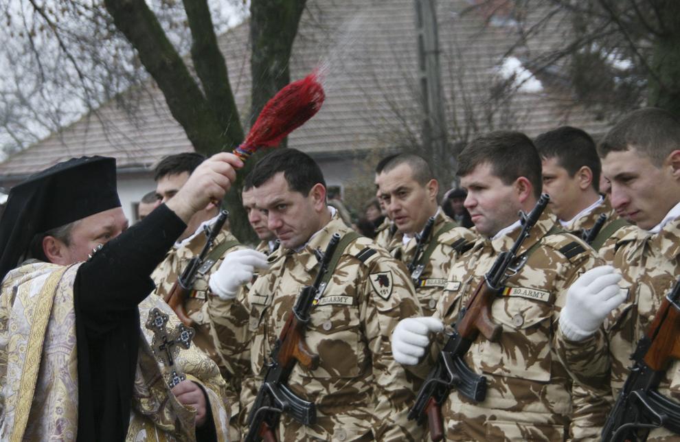 """Un preot îi stropeşte cu agheasmă pe militarii batalionului 151 Infanterie """"Lupii Negri"""", în timpul ceremonialului militar şi religios prilejuit de plecarea acestora în misiunea Iraqi Freedom, în Iaşi, vineri, 18 ianuarie 2008."""
