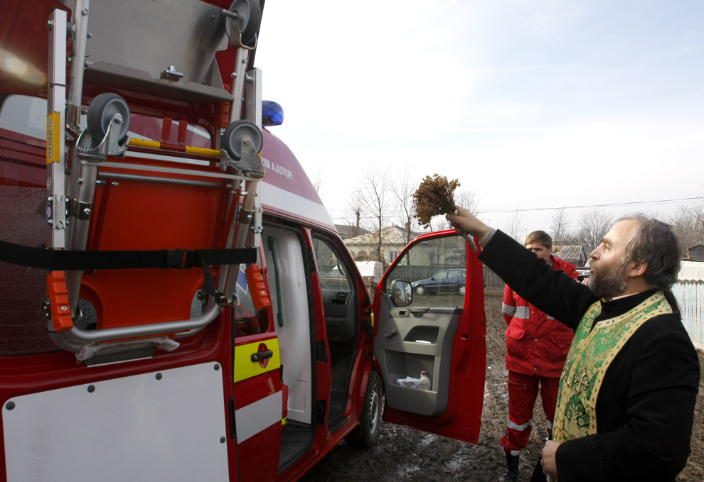 Un preot sfinţeşte o ambulanţă, cu ocazia inaugurării unei substaţii SMURD în comuna Şipote, Iaşi, sâmbătă, 2 februarie 2008.