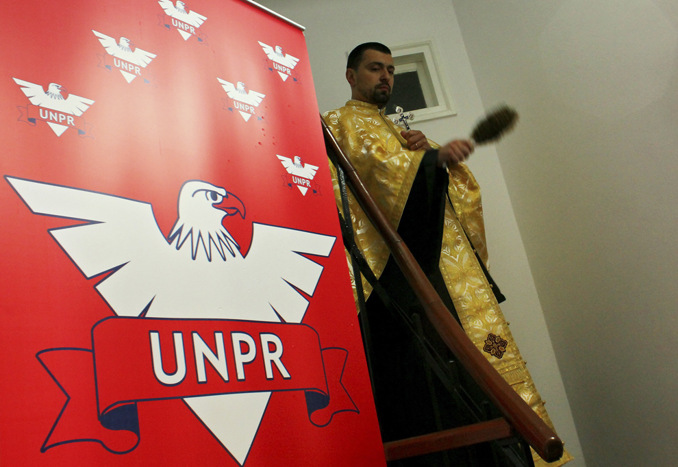 Un preot oficiază sfeştania, înainte de şedinţa Biroului Permanent Naţional al UNPR, la noul sediu al partidului, în Bucureşti, marţi, 18 mai 2010.