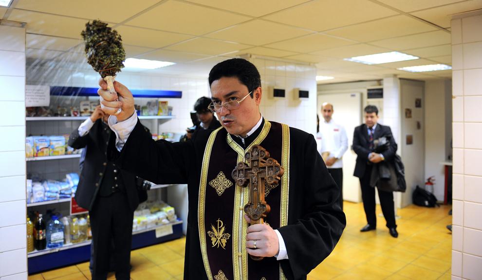 Un preot ţine o slujbă la deschiderea unui magazin social, în Bucureşti, miercuri, 20 octombrie 2010.