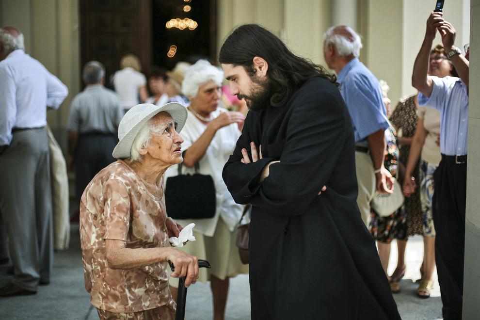Diaconul Zareh Arachelian stă de vorbă cu batrâna Surpic, în faţa Catedralei Armene Sfinţii Arhangheli Mihail şi Gavril (1911-1915) din Bucureşti.