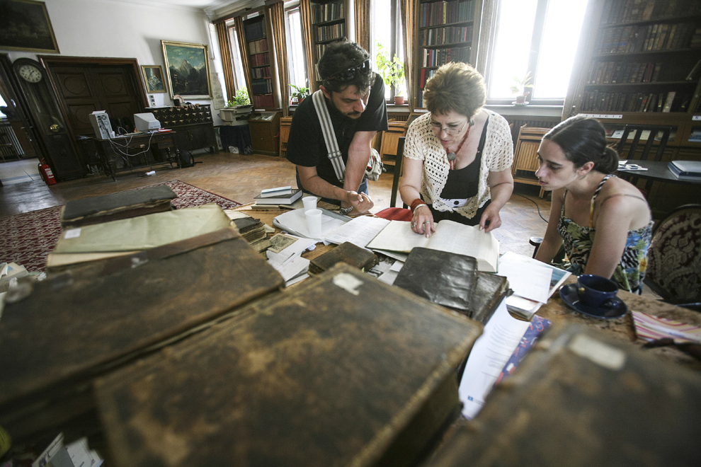 Arshaluys Paronyan (C) împreună cu fiica sa Lusine Navasardyan (D) şi preotul Ezras Bogdan (S) studiază conţinutul unor carţi vechi scrise în limba armeană, în incinta bibliotecii armene Hovsep şi Victoria Dudian.