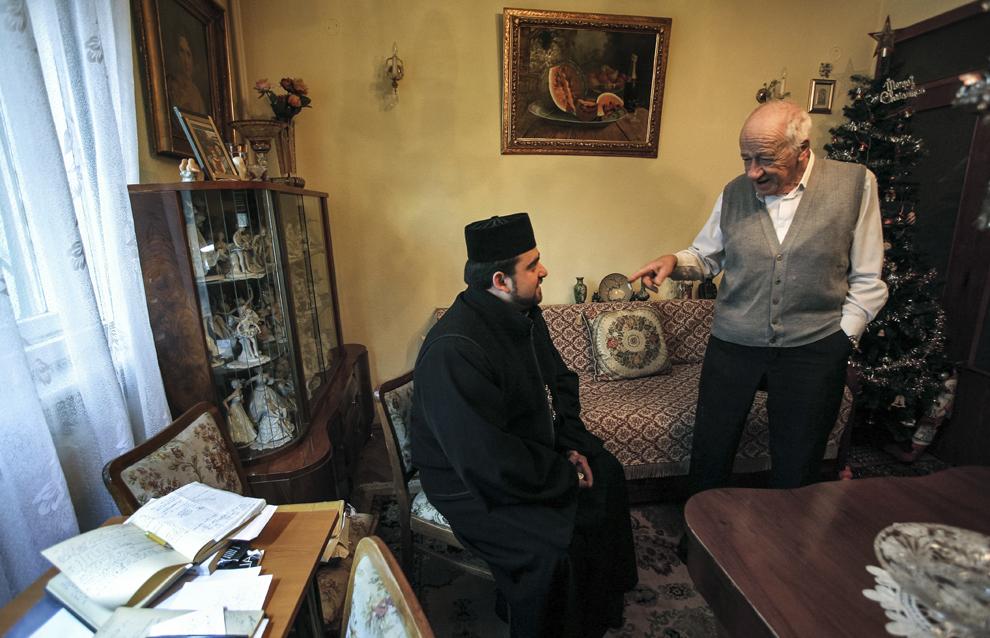 Minasian Eduard Antranik (D) discută cu preotul Hayazat Martikyan (S) în casa sa din Piteşti, România.
