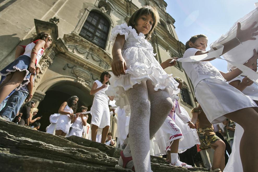 Un grup de copii participă la procesiunea religioasă organizată cu ocazia Srbatorii Sfintei Maria, în faţa Catedralei Armeano-Catolice Sfânta Elisabeta (1766-1791) din Dumbrăveni.