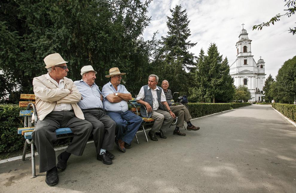 Câţiva barbaţi stau de vorba pe o bancă din parcul Catedralei Armeano-catolice Sfânta Treime (1748-1789) din Gherla.