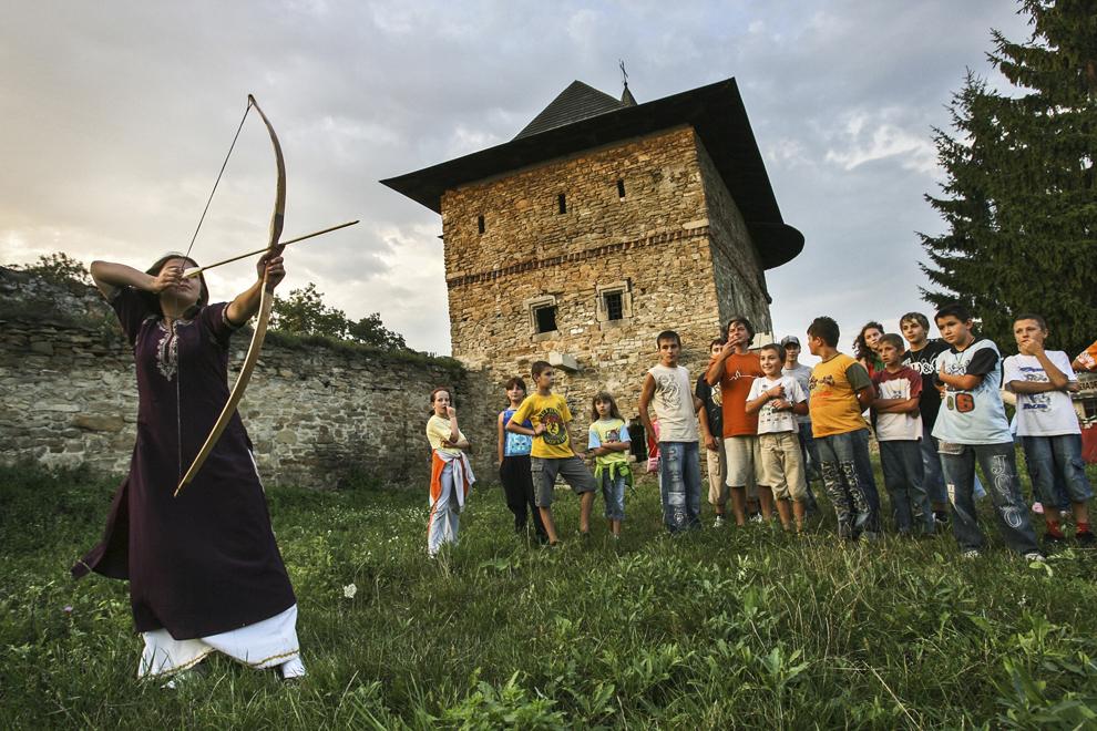 """Un grup de elevi ai şcolii de tir cu arc englezesc – Ordinul Basarabilor participă la evenimentul """"Serile de artă medievală din Cetatea de Scaun a Moldovei"""", organizat în incinta Mânăstirii armene Zamca (1606) din Suceava."""