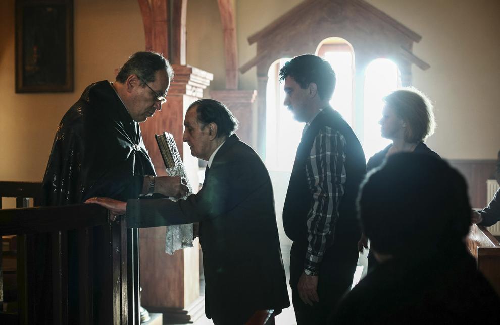 Parintele Avedis Mandalian şi enoriaşii săi, în timpul unei slujbe religioase, în Biserica armeană din Constanţa.