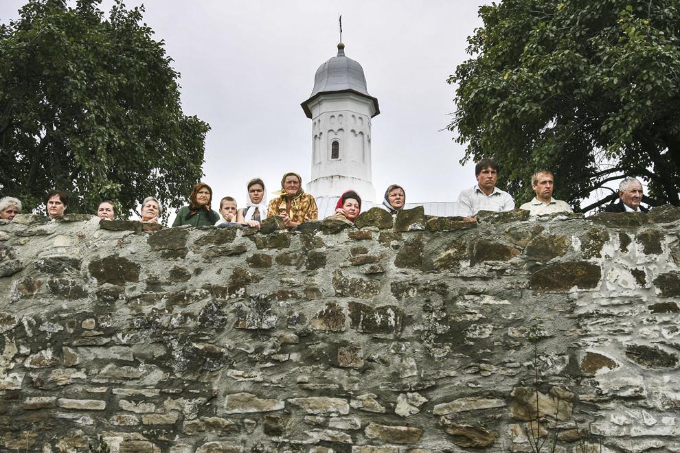 Pelerini privesc procesiunea organizată cu ocazia Sărbătorii Adormirea Maicii Domnului de pe zidul Mânăstirii Hagigadar (1512), Suceava.