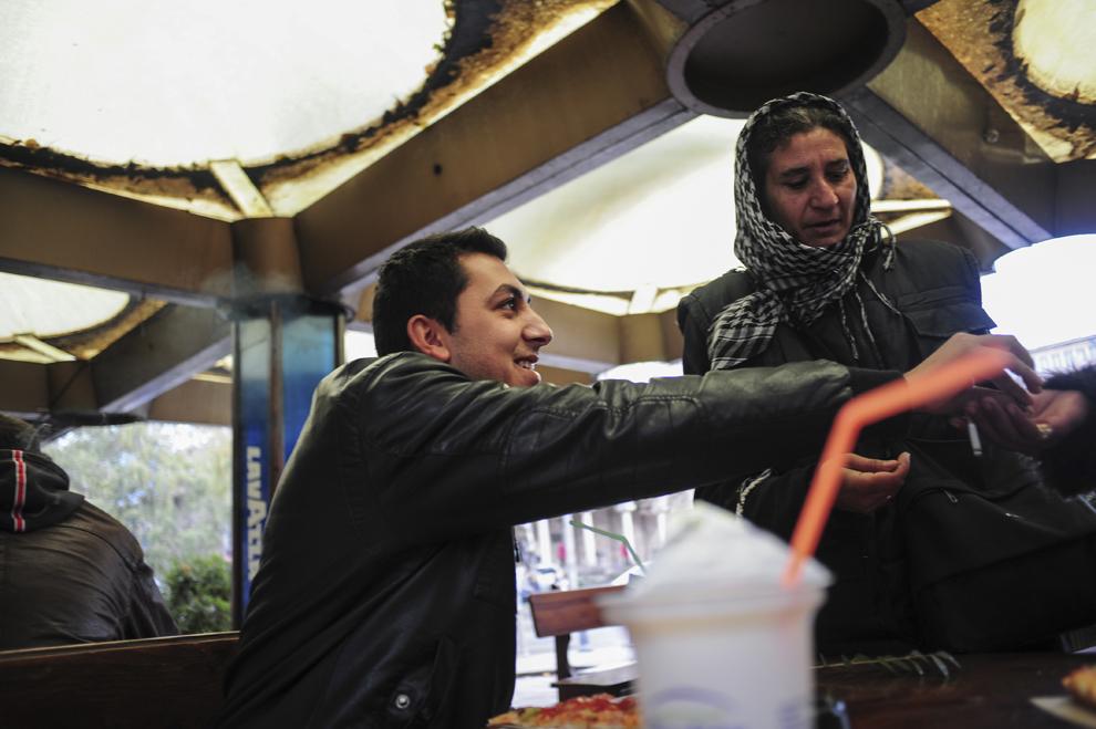 """Atanas """"Nasko"""" Stoyanov îi întinde bani unei cerşetoare de origine romă într-un restaurant din Sofia, Bulgaria."""