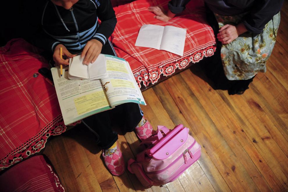 Mari, 9 ani, este ajutată de bunica ei cu temele, în casa familiei de romi căldărari Borisova, din Simitli, Bulgaria.