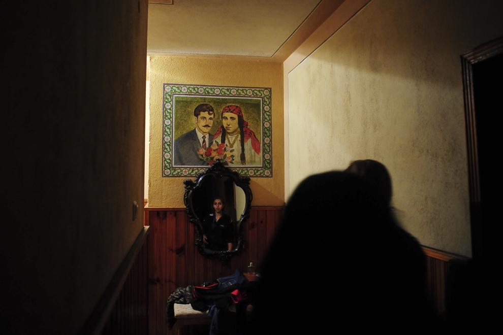 Maryana Borisova trece pe un hol al casei părinţilor ei unde poate fi văzută o pictură care îi înfăţişează pe bunicii ei, romi căldărari, care s-au stabili şi au construit casa familiei Borisova, în Similti, Bulgaria.