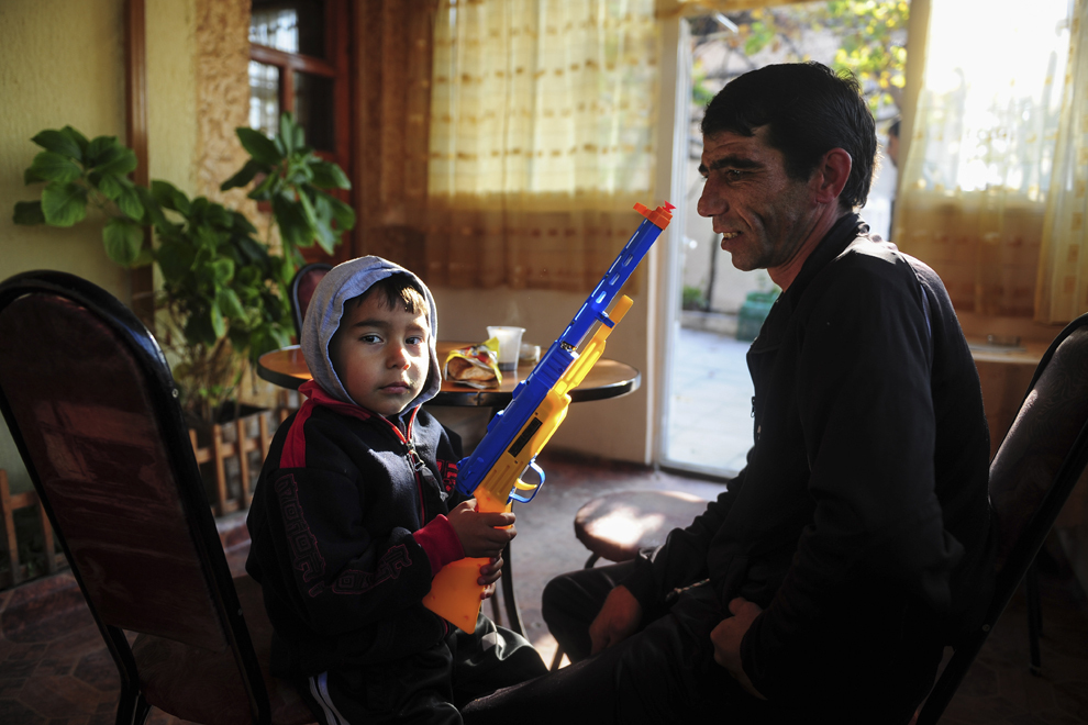 Un copil de etnie roma priveşte spre cameră în timp ce îl însoţeşte pe tatăl său într-un bar din Simitli, acolo unde acesta îşi bea cafeaua.