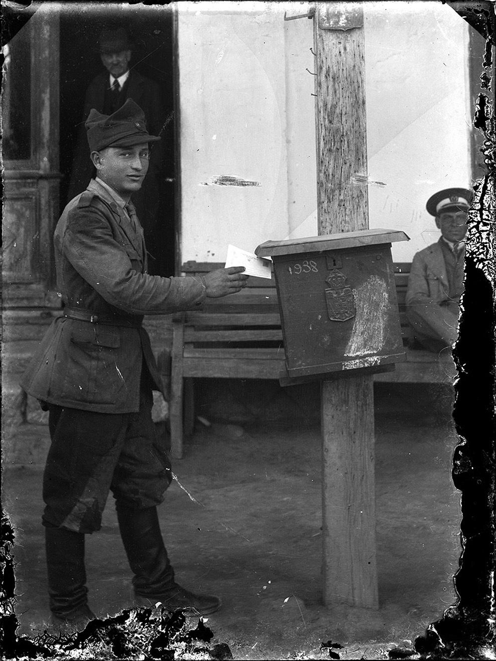 Soldat punând o scrisoare la cutia poştală.
