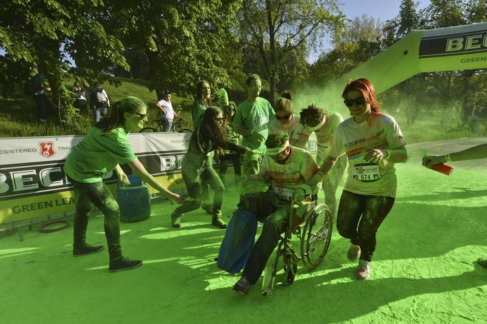 """Un bărbat în scaun cu rotile este împins de alergători în timpul maratonului 5K """"Color Run"""", în parcul Tineretului din Bucureşti, sâmbătă, 26 aprilie 2014."""
