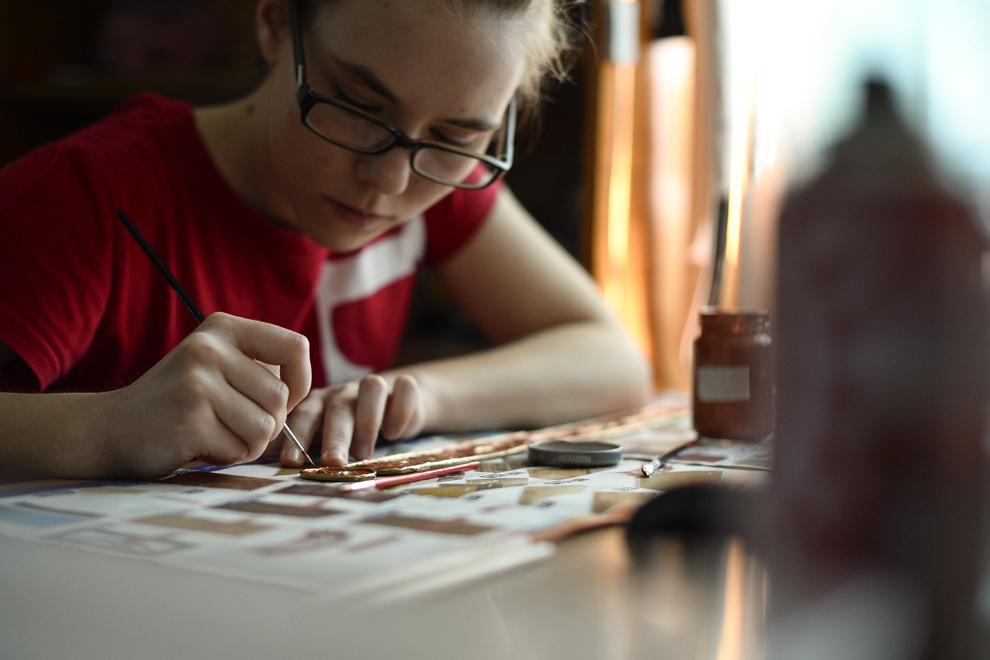 Miruna Petraru, elevă, 17 ani, pictează cureaua costumului în care o va personifica pe eroina Leona din jocul League of Legends, în Bucureşti, joi, 23 aprilie 2014.