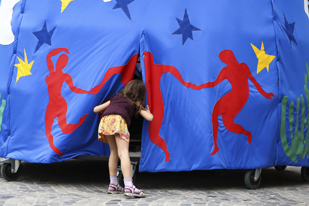 """O fetiţă urmăreşte spectacolul """"The Divas"""" al companiei Transe Expres, desfăşurat în timpul Festivalului Internaţional de Teatru de Stradă """"B-FIT in the Street"""", în Bucureşti, joi, 29 mai 2014."""