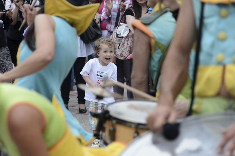 """Un copil reacţionează în timpul spectacolului """"Camaleons Drums Team"""", al companiei Compagnie Cameleon, în prima zi a B-FIT in the Street! - Festivalul Internaţional de Teatru de Stradă Bucureşti, în Piaţa Universităţii, joi, 29 mai 2014."""