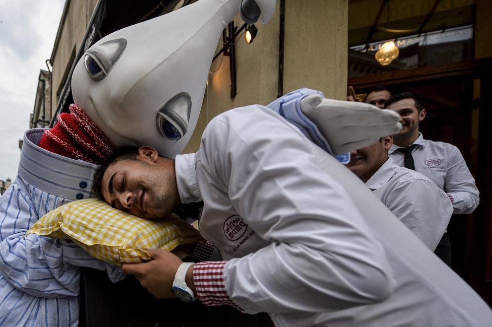 """Un angajat al unui restaurant se preface că doarme în timpul spectacolului """"Dede's"""" al companiei Groupe Demons & Merveilles, în prima zi a B-FIT in the Street! - Festivalul Internaţional de Teatru de Stradă Bucureşti, în Piaţa Roma, joi, 29 mai 2014."""