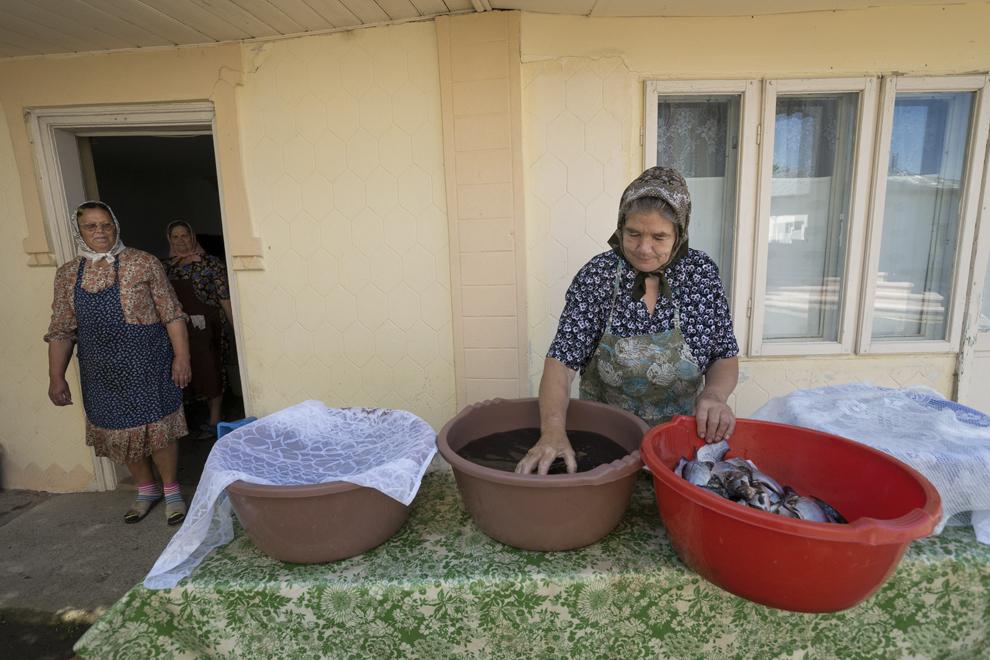 Femeile din sat spală peştele pentru masa de duminică, de la slujba Rusaliilor, atunci când toţi enoriaşii prezenţi vor mânca la biserică.